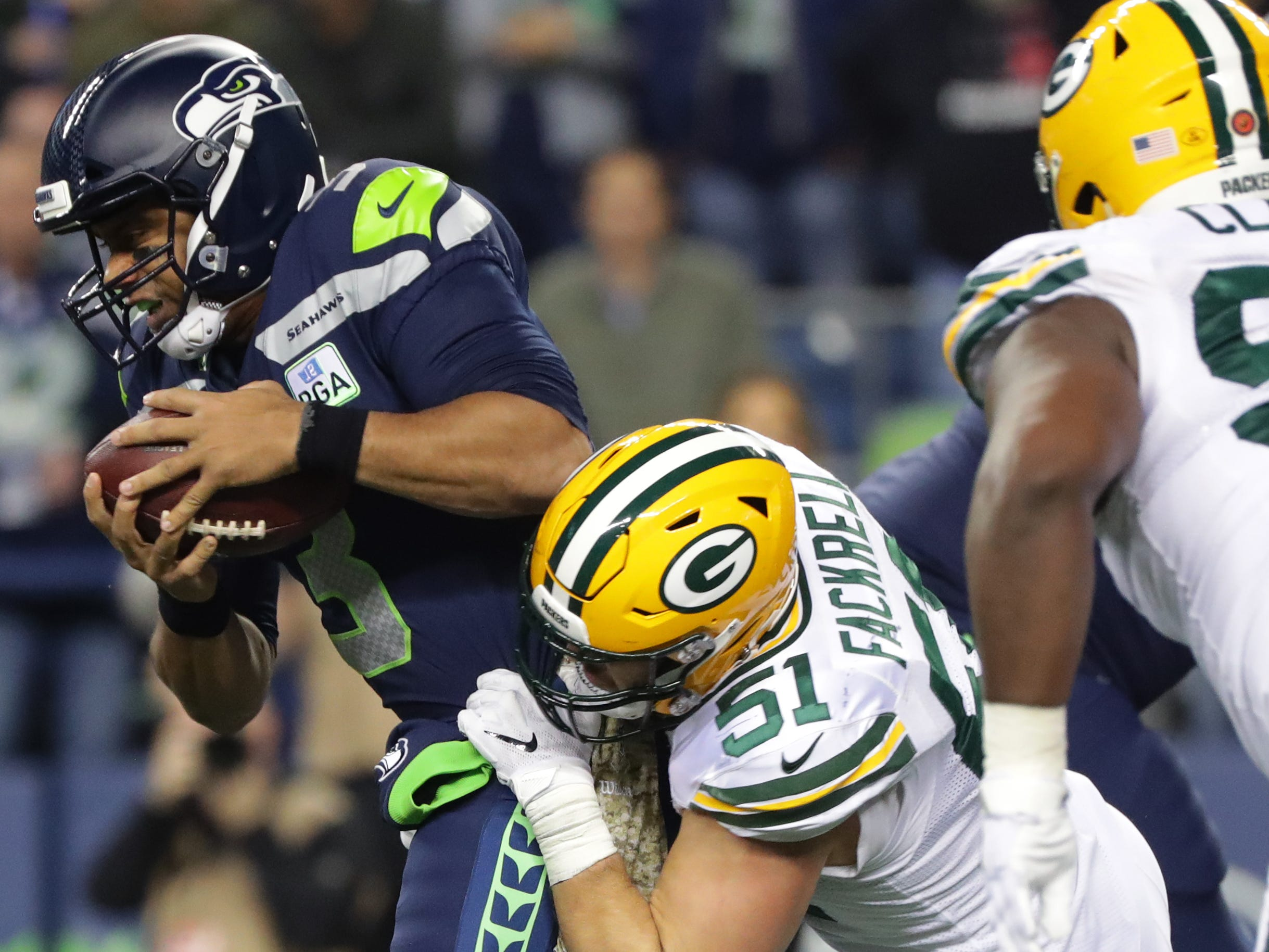 Seattle Seahawks quarterback Russell Wilson (3) is sacked by Green Bay Packers linebacker Kyler Fackrell (51) during the third quarter of their game Thursday, November 25, 2018 at CenturyLink Field in Seattle, Wash.