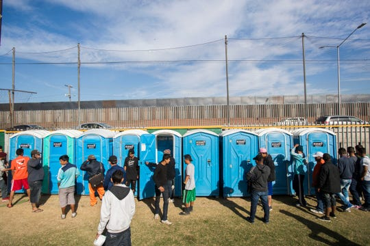 About 2,000 migrants have arrived at the Benito Juarez sports complex in Tijuana as of Friday, there were only two bathrooms available for women and men. In this photo migrants use portable bathrooms that were brought in on Friday after the lack of bathrooms for the migrants was voiced as a concern by human rights groups observing the migrants' shelter.