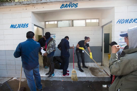 Cleaning crews try to manage the two bathrooms Nov. 16, 2018, that area available for migrants staying at the Benito Juarez sports complex in Tijuana, Mexico, as they await a chance to seek asylum in the United States.