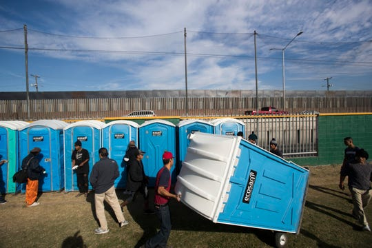 Migrants at the Benito Juarez sports complex in Tijuana, Mexico, use portable bathrooms that were brought in Nov. 16, 2018, after human rights groups observing the caravan's progress expressed concern at the lack of bathrooms there.