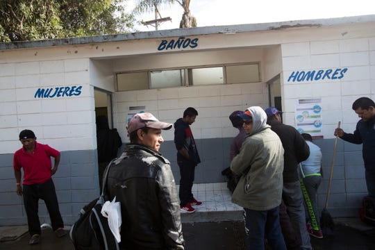 Nearly 2,000 migrants have arrived at the Benito Juarez sports complex in Tijuana as of Friday, there were only two bathrooms available for women and men. In this photo cleaning crews try to manage the two bathrooms available for the migrants.