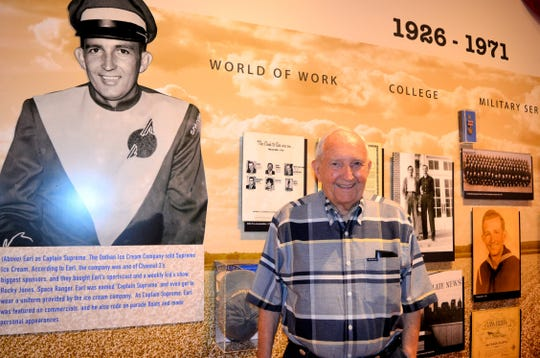 "Earl Hutto poses in front of the exhibit ""Cotton Fields to Congress,"" which chronicles his life."