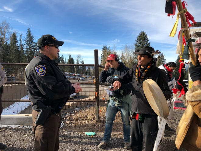 A Coconino County sheriff's deputy talks with protesters at Snowbowl ski resort Nov. 16, 2018. The protesters were turned away from entering the resort grounds.