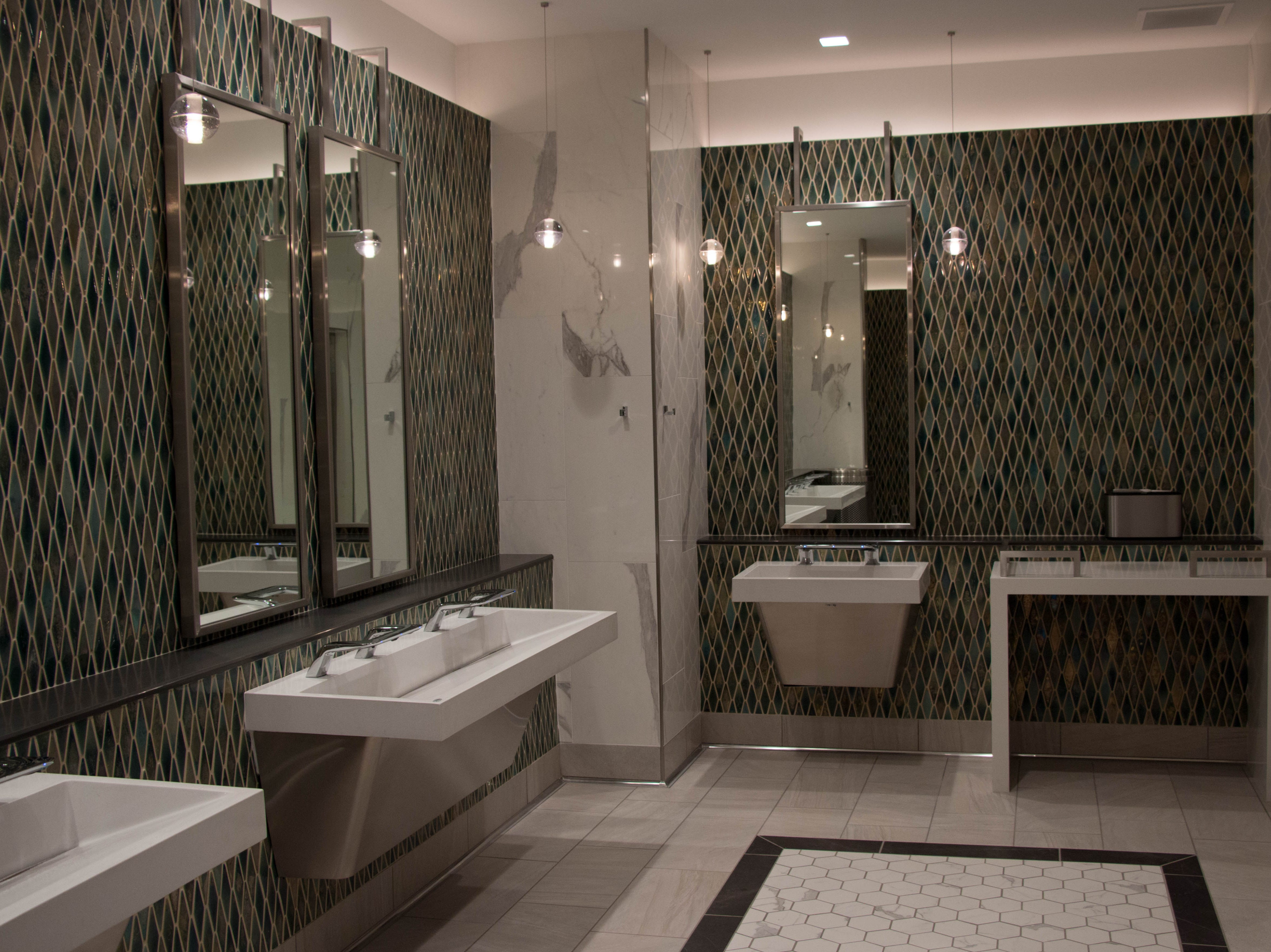The men's bathroom in the updated luxury wing feature handpainted tile, 3-in-1 sinks and a changing table.