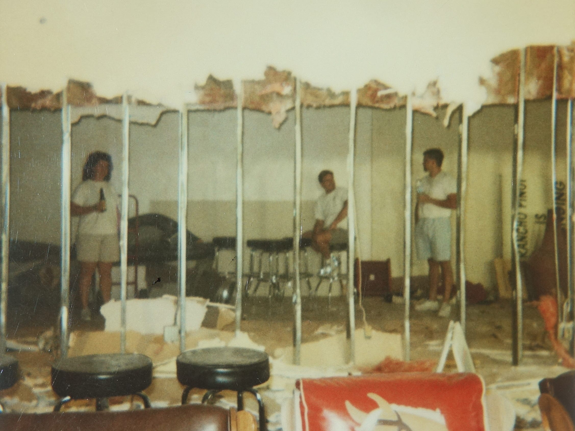 Chrysa Robertson and others demolish the wall to expand Rancho Pinot's Scottsdale location in 1998.