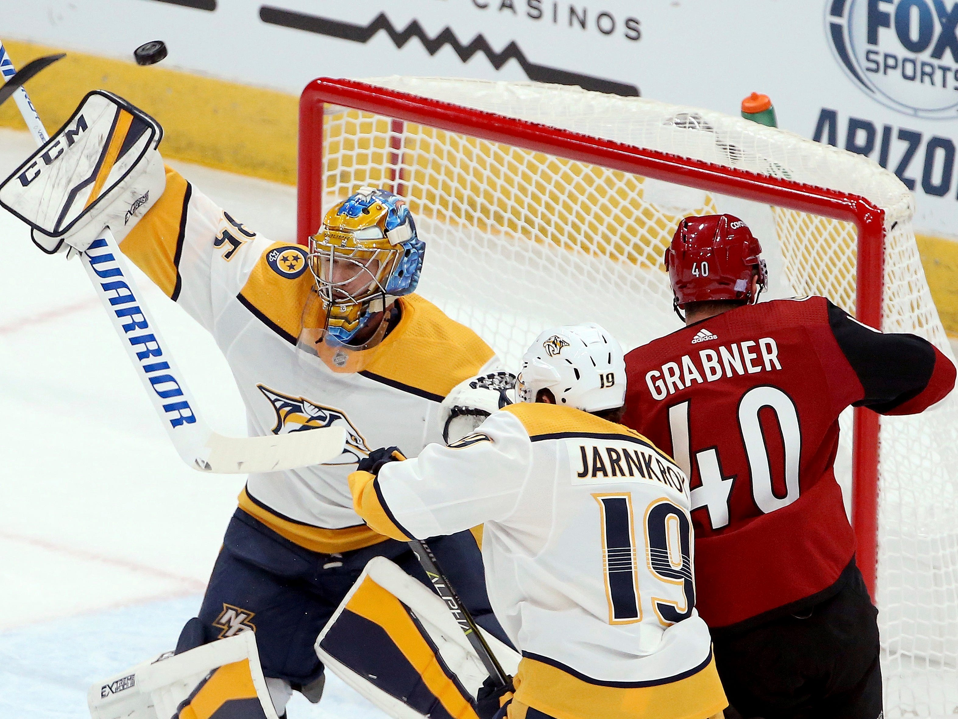 Nashville Predators goaltender Pekka Rinne, left, makes a save on a shot as Arizona Coyotes right wing Michael Grabner (40) battles with Predators center Calle Jarnkrok (19) during the first period of an NHL hockey game Thursday, Nov. 15, 2018, in Glendale, Ariz. (AP Photo/Ross D. Franklin)