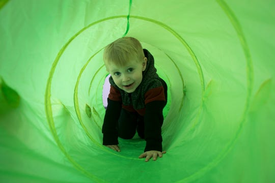 A preschool student crawls through a tube in the gym Nov. 13, 2018, at the Young Mind Center in Phoenix.