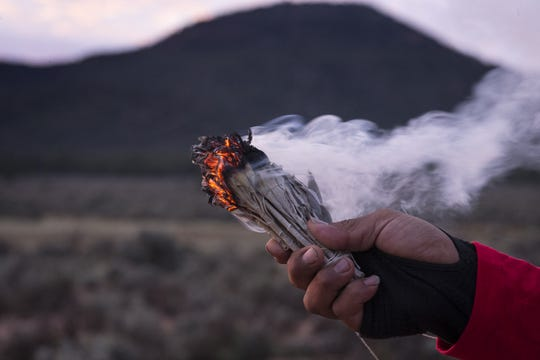 Uqualla, a Havasupai medicine man, burns sage during a morning prayer during Havasupai Tribe's Intertribal Spiritual Gathering at Red Butte in October.