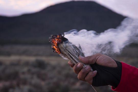 Uqualla, a Havasupai medicine man, burns sage during a morning prayer during Havasupai Tribe's Intertribal Spiritual Gathering at Red Butte in October.