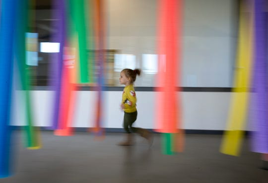 A preschool student walks through the sensory forest Nov. 13, 2018, at the Young Mind Center in Phoenix.