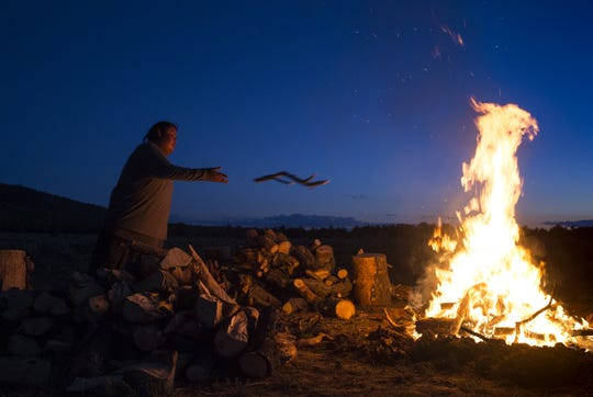 Nicholas Sinyella tends the fire on an October night during Havasupai Tribe's Intertribal Spiritual Gathering at Red Butte.
