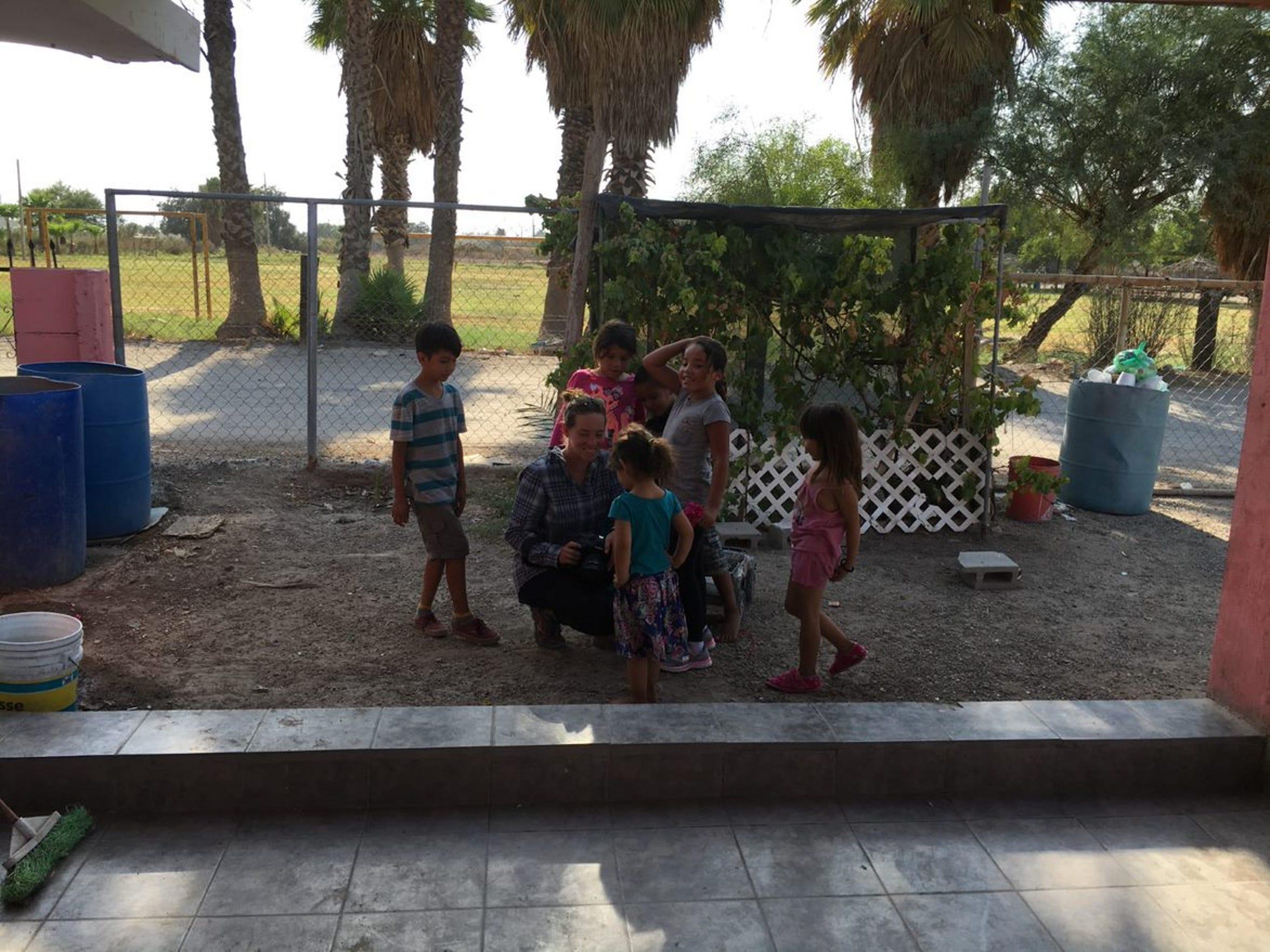 Zoe Meyers muestra algunas de sus fotos con niños que juegan en un patio cercano a una fábrica en Mexicali.
