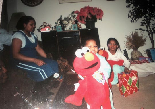Mikaela McNeil and her sister, Mariana McNeil, open gifts on Christmas Day of 2004 as their mother, Darshima McNeil, looks on.