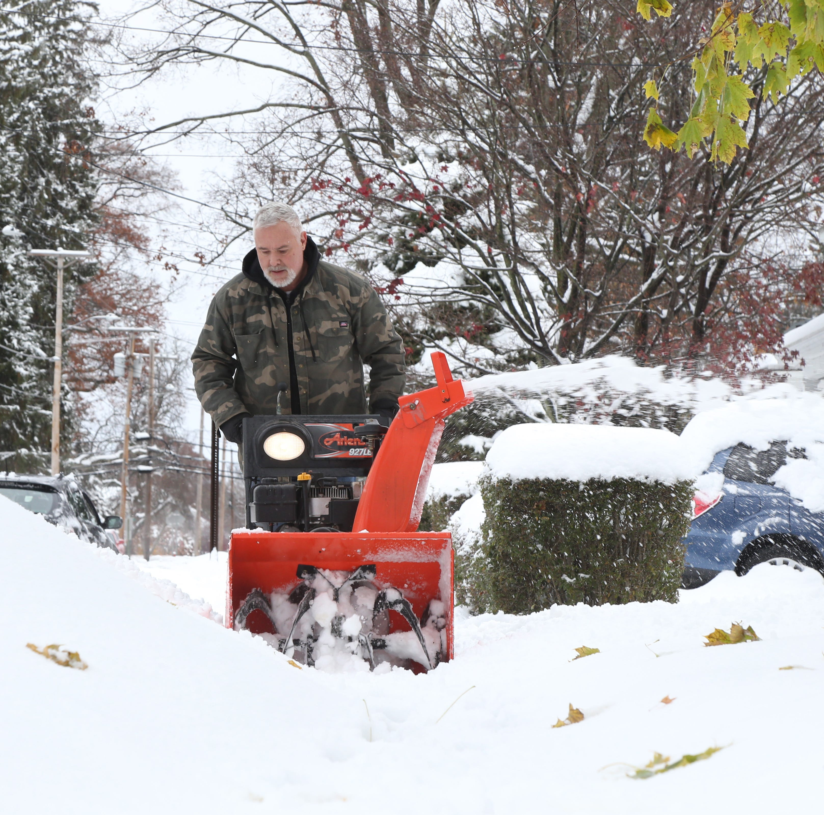 Wayne MacIsaac uses his snow blower to clear snow outside his home in the Village of Wappingers Falls on November 16, 2018.