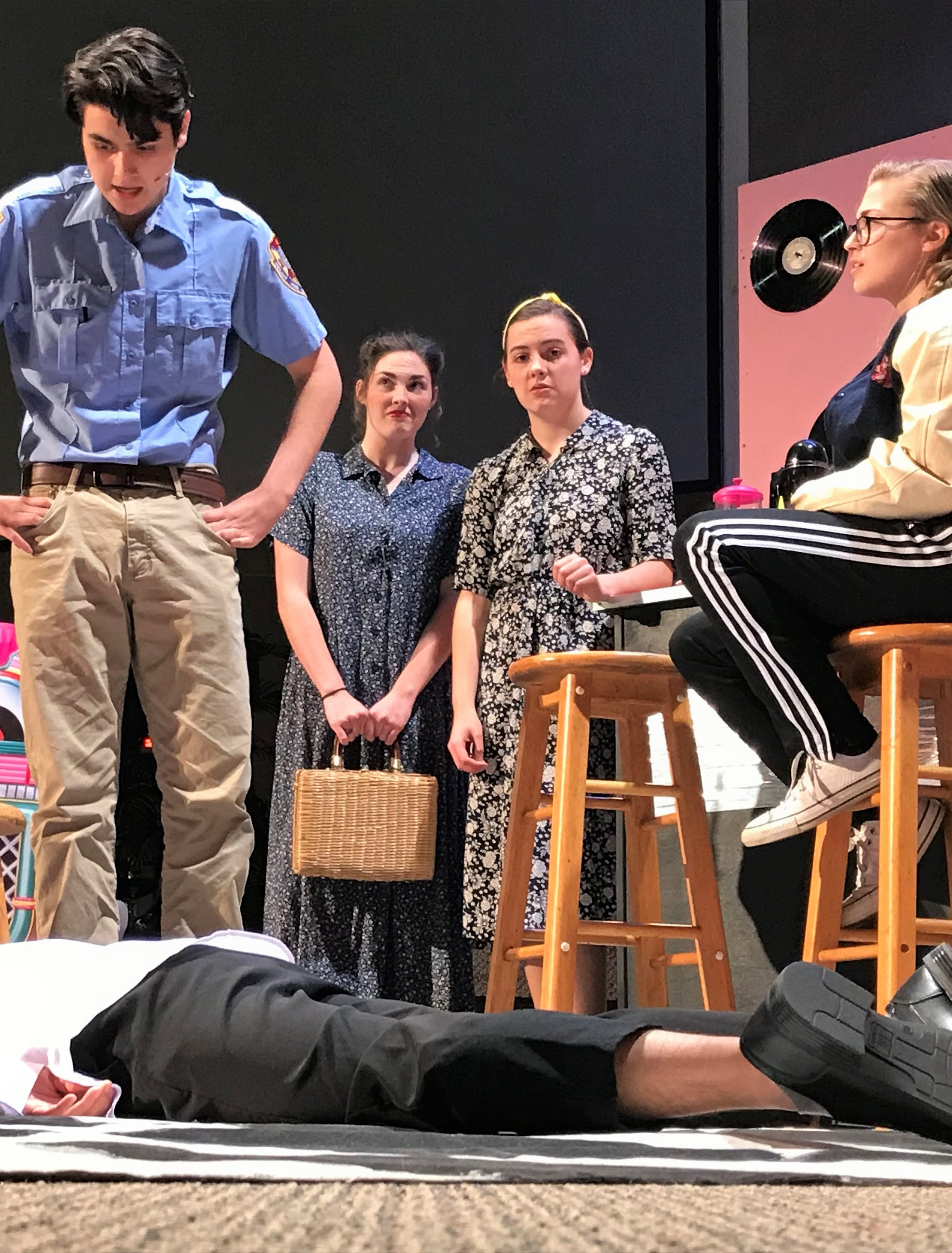 "A character lies dead on the floor of the malt shop in a scene in Cumberland Valley Christian School's rendition of ""Murder of the Malt Shop,"" during a dress rehearsal on Friday afternoon. Pictured are, from left: David Jeong (on the floor), Gianni Castellano, Bethany Snyder, and Marlee Stake."