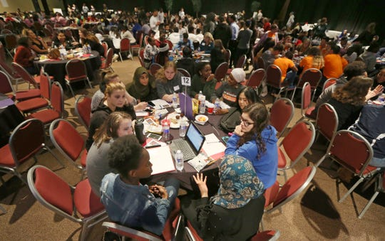 Marah Ali, a sophomore at West Irondequoit, bottom right, leads a discussion on race at her table of West Irondequoit schoolmates during the Individual School Work Session at the ROC 2 Change student summit on race.
