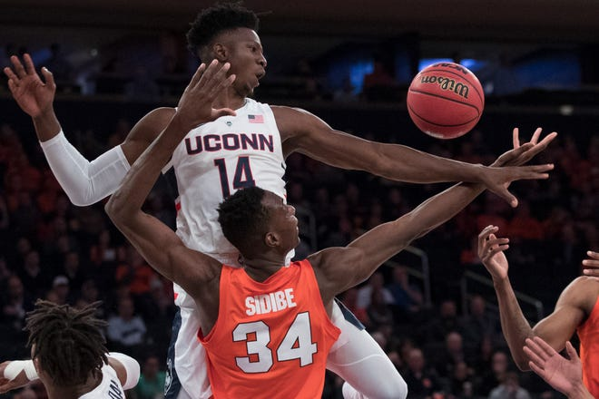Connecticut forward Kassoum Yakwe (14) and Syracuse forward Bourama Sidibe (34) vie for a rebound during the first half of an NCAA college basketball game in the 2K Empire Classic, Thursday, Nov. 15, 2018, at Madison Square Garden in New York. (AP Photo/Mary Altaffer)