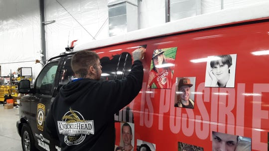 An employee of Vital Signs in Webster adds the photo of another person who died from an opioid overdose in Monroe County to a Gates Police Department van.