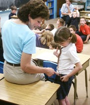 "2005: Teacher MaryAnn Wasnock looks at Emily Hayes' snake during ""pet day"" at St. Charles Borromeo School."