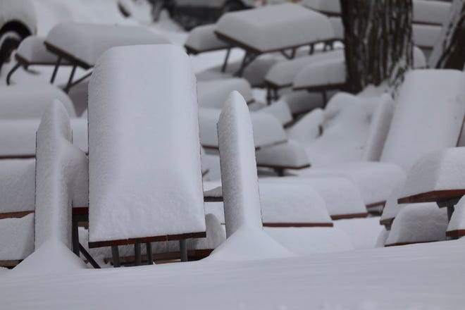 Picnic tables are almost hidden in the snow