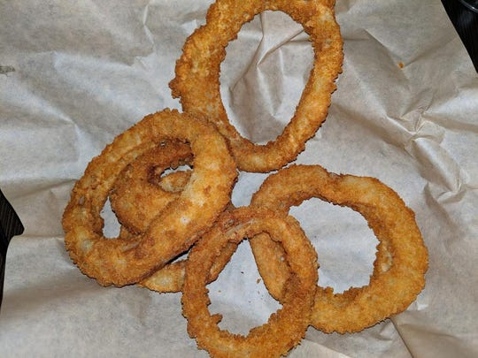 The onion rings at The Angry Goat feature thick onion slices with crisp breading.