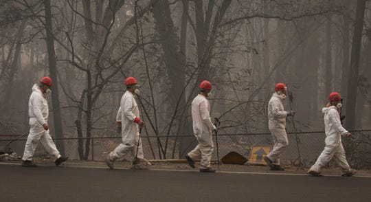Search and rescue personnel walk to their next destination to comb through debris searching for remains in a neighborhood near Pentz Road in Paradise, CA, after the Camp Fire devastated the area.