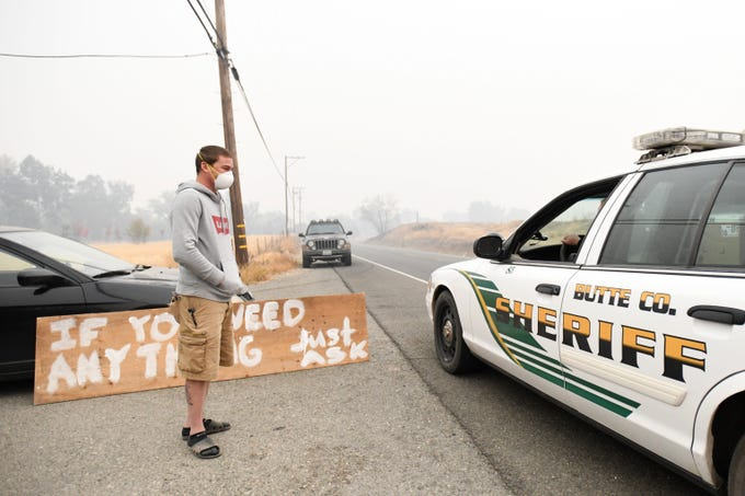 Well inside the evacuation zone surrounding the California town of Paradise, resident Chris Jones thanks a Butte County sheriff's deputy for the work she and other first responders are doing. Jones is one of the few still living inside the evacuation zone.
