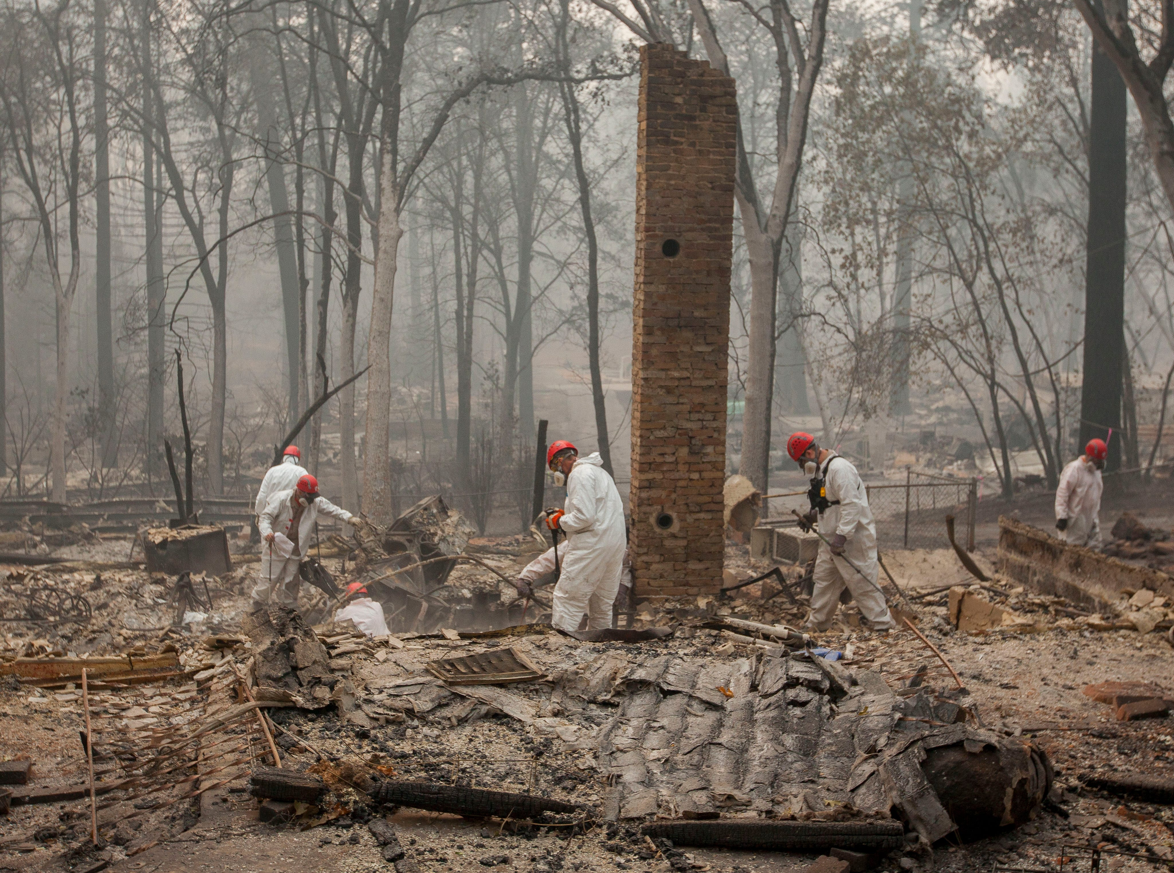 Search and rescue personnel comb through debris searching for remains in a neighborhood near Pentz Road in Paradise, CA, after the Camp Fire devastated the area.