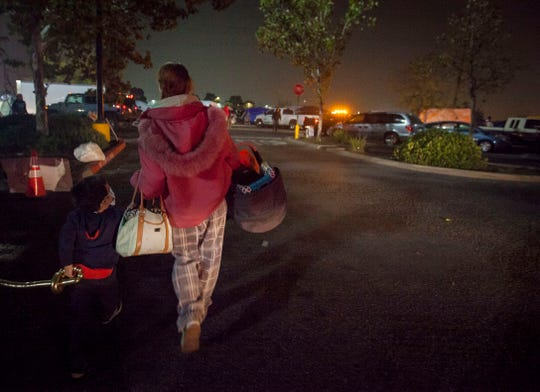 File photo - Jasmin Hamburg, center, in November 2018 carries her youngest son Aiden, 10 months and holds the hand of her older son Lucas, 4, as she walks back to the tent compound next to the Walmart in Chico, CA. The parking lot and field next to it temporarily became a refuge for evacuees of the Camp Fire.
