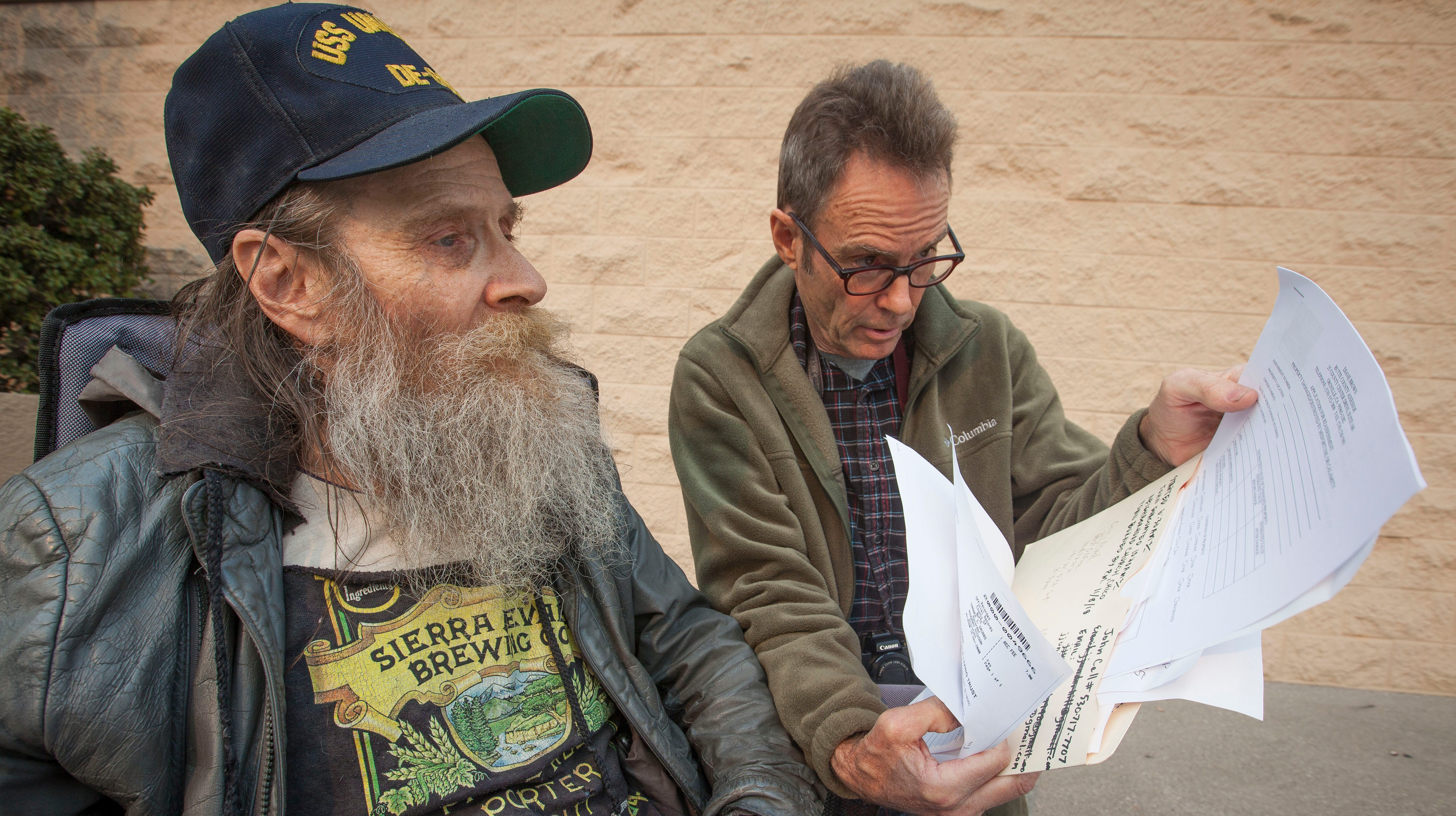 Larry Underhill, right, of Los Angeles, goes over paperwork with his brother John Jay Underhill, of Paradise, after they left the FEMA assistance center that opened in the old Sears store in the Chico Mall Friday, Nov. 16, 2018. John lost his home, most of his personal identification information and all of his belongings when the Camp Fire devastated the area. The center is set up for fire survivors to have access to local, state and federal assistance to begin the process of rebuilding.