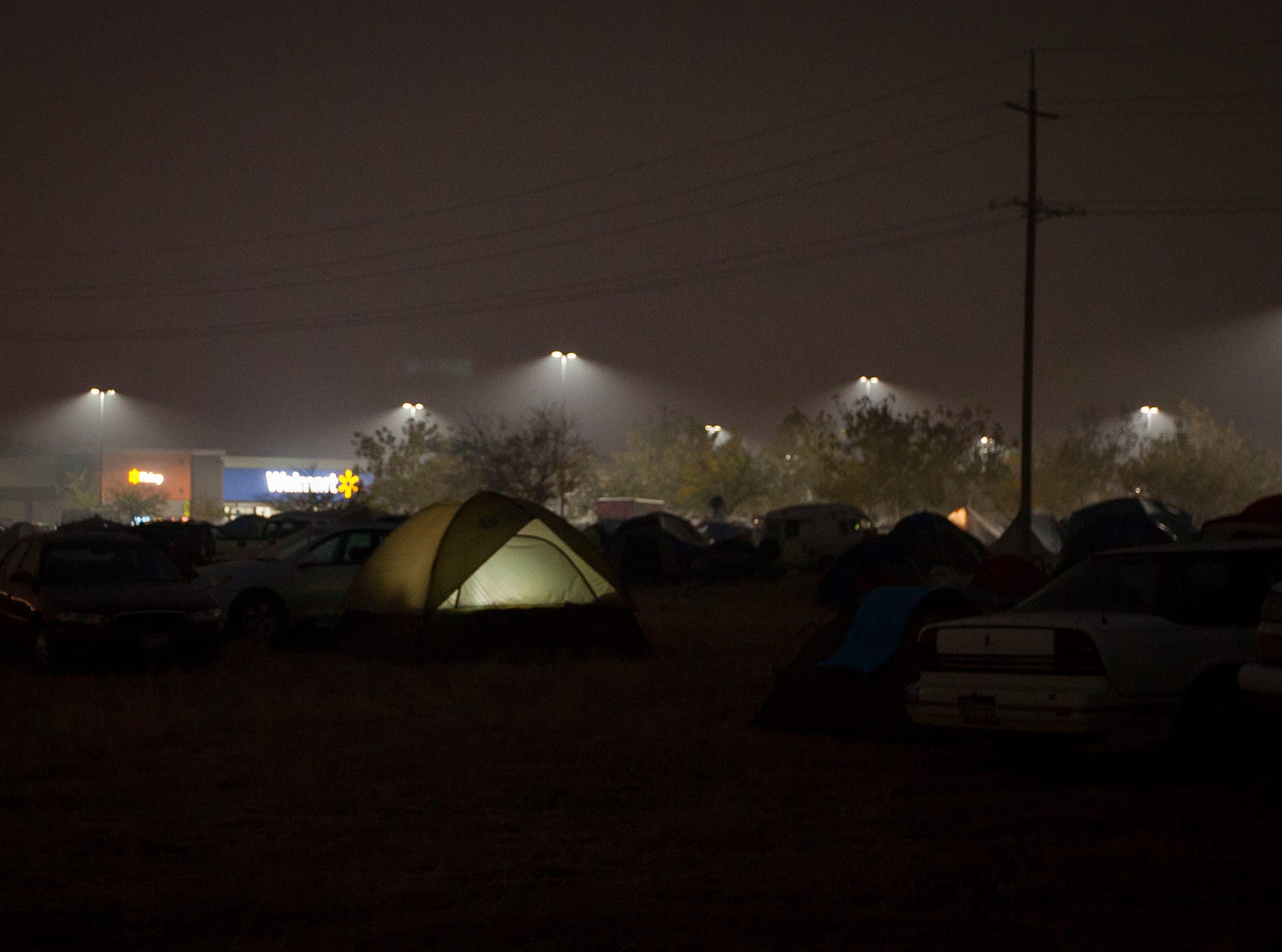 A tent glows from a light inside as people live in a make-shift tent compound next to the Walmart in Chico, CA. The parking lot and field next to it have become a refuge for evacuees of the Camp Fire which devastated Paradise. Officials are closing the area on Sunday and working to find a more sustainable housing solution for those affected by the fire.