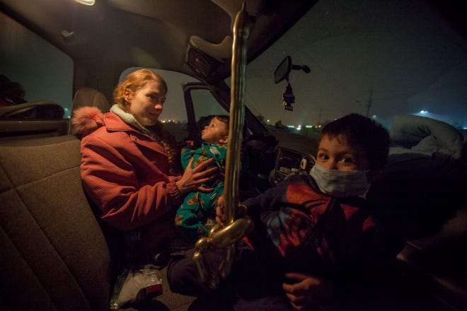 Jazmin Hamburg, left, sits in the cab of a pick-up truck to stay warm with her two sons Aiden, 10 months, center and her older son Lucas, 4, in the tent compound next to the Walmart in Chico, CA. The parking lot and field next to it have become a refuge for evacuees of the Camp Fire which devastated Paradise. Officials are closing the area on Sunday and working to find a more sustainable housing solution for those affected by the fire.