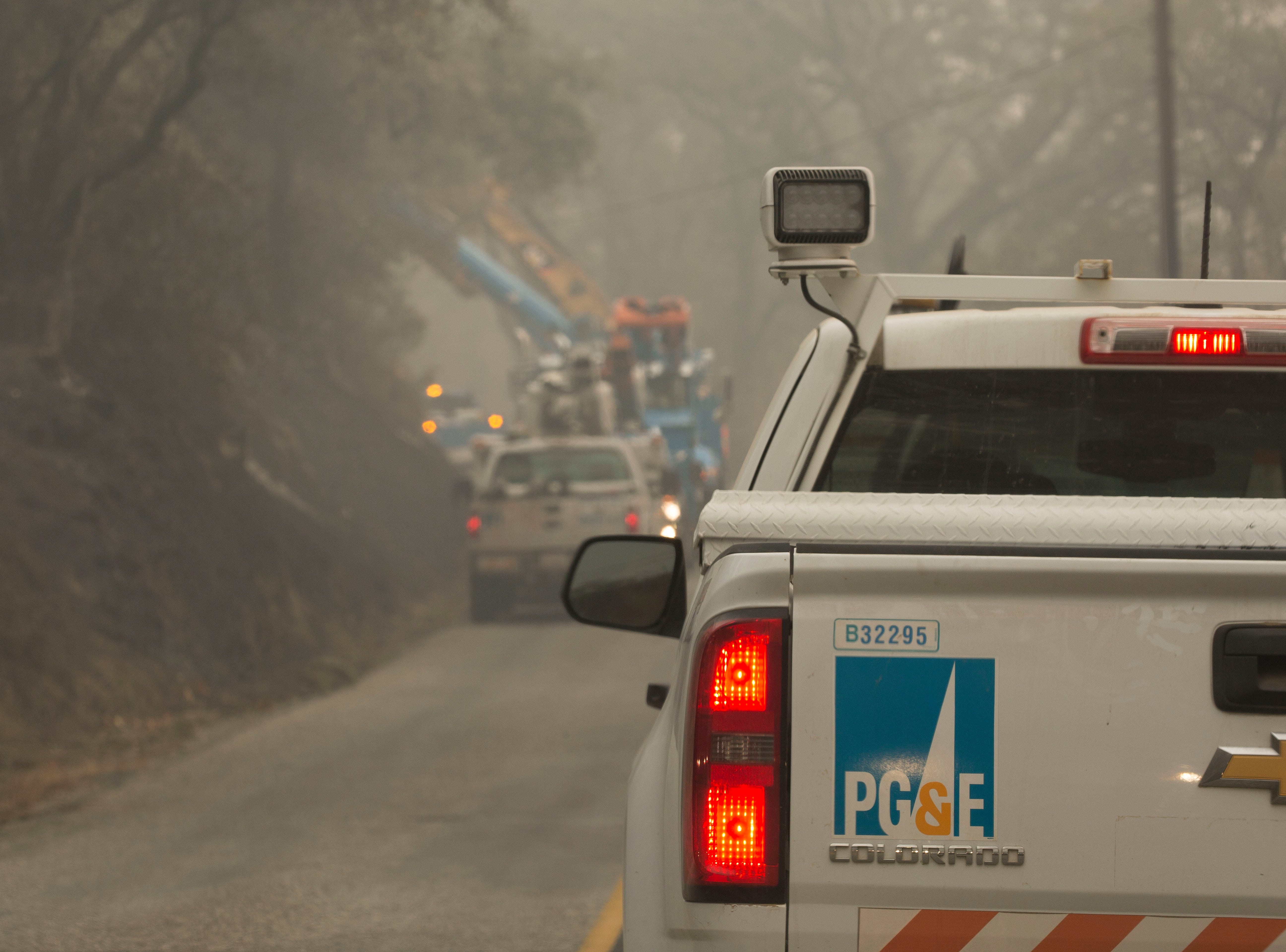 Workers from PG&E work to replace power poles along Honey Run Road in Paradise, Thursday November 15, 2018.