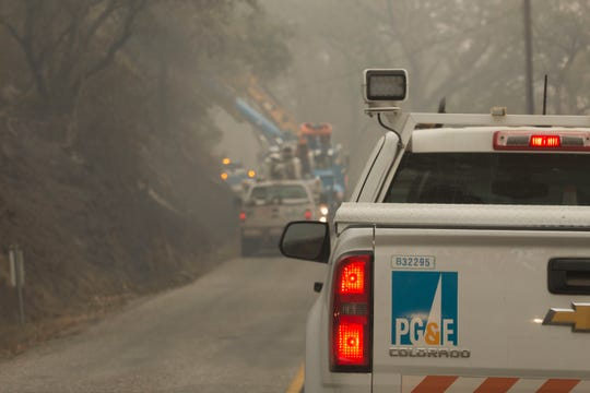 Workers from PG&E replace power poles along Honey Run Road in Paradise on Nov. 15, 2018.