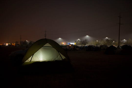 A tent glows from a light inside as people live in a make-shift tent compound next to the Walmart in Chico. The parking lot and field next to it have become a refuge for evacuees of the Camp Fire which devastated Paradise. Walmart told evacuees to leaves its Chico parking lot by 1 p.m. Sunday, Nov. 18.