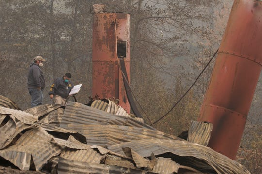 Officials with Butte County, FEMA and California Office of Emergency Services inspect what used to be the Honey Run Covered Bridge Thursday November 15, 2018. The historic bridge completely burned during the Camp Fire in Paradise, CA.