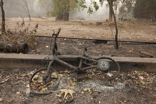 A burned bicycle sits on the edge of a property along Honey Run Road after the Camp Fire devastated the area.