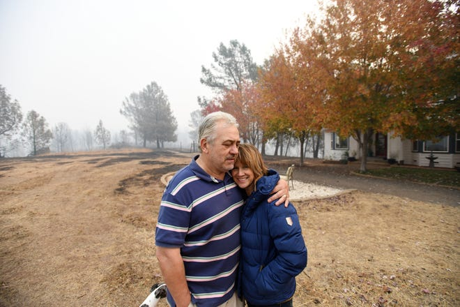 Rhys and Valerie Owen of Paradise, California, stand in the front yard of their home, which narrowly escaped the Camp Fire. Flames spared little on the property, but the home, barn and chicken coop are still standing.