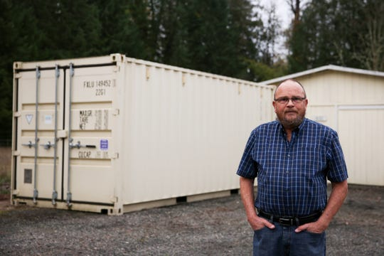 The leading vote getter for mayor, Daniel Tucker, stands by his shipping container in front of his house on Thursday, Nov. 15, 2018, in Gates. The city council of Gates considered bringing an ordinance to ban shipping containers which inspired Tucker to run.
