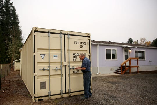 The leading vote getter for mayor, Daniel Tucker, opens his shipping container in front of his house on Thursday, Nov. 15, 2018, in Gates. The city council of Gates considered bringing an ordinance to ban shipping containers which inspired Tucker to run.