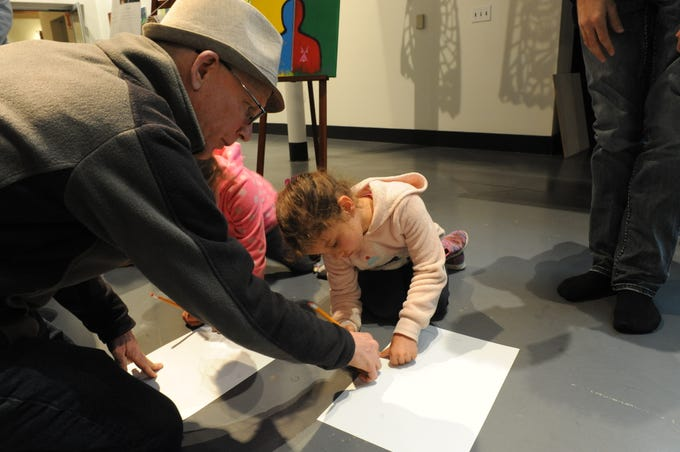 Ernest Stromberg, a CSUMB professor, helps his daughters Luna and Annalise make their moccasins.