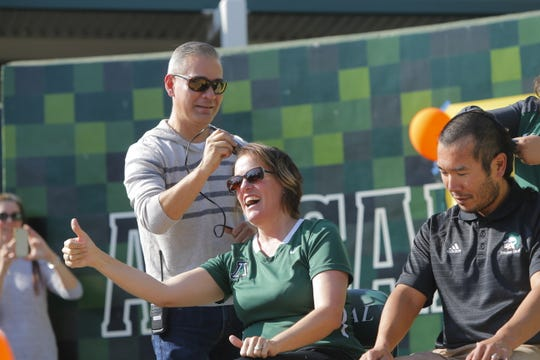 Spouses and Alisal High School faculty Jennifer and Ryoji Bunden get their head shaved by Enrique Lopez, the school's assistant principal, on Friday. Bunden promised she'd shave her head if the students brought in enough donations for the Food Bank for Monterey County, which they did.