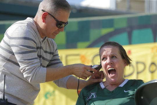 Alisal High School Activities Director Jennifer Bunden gets her head shaved by Enrique Lopez, the school's assistant principal, on Friday. Bunden promised she'd shave her head if the students brought in enough donations for the Food Bank for Monterey County, which they did.