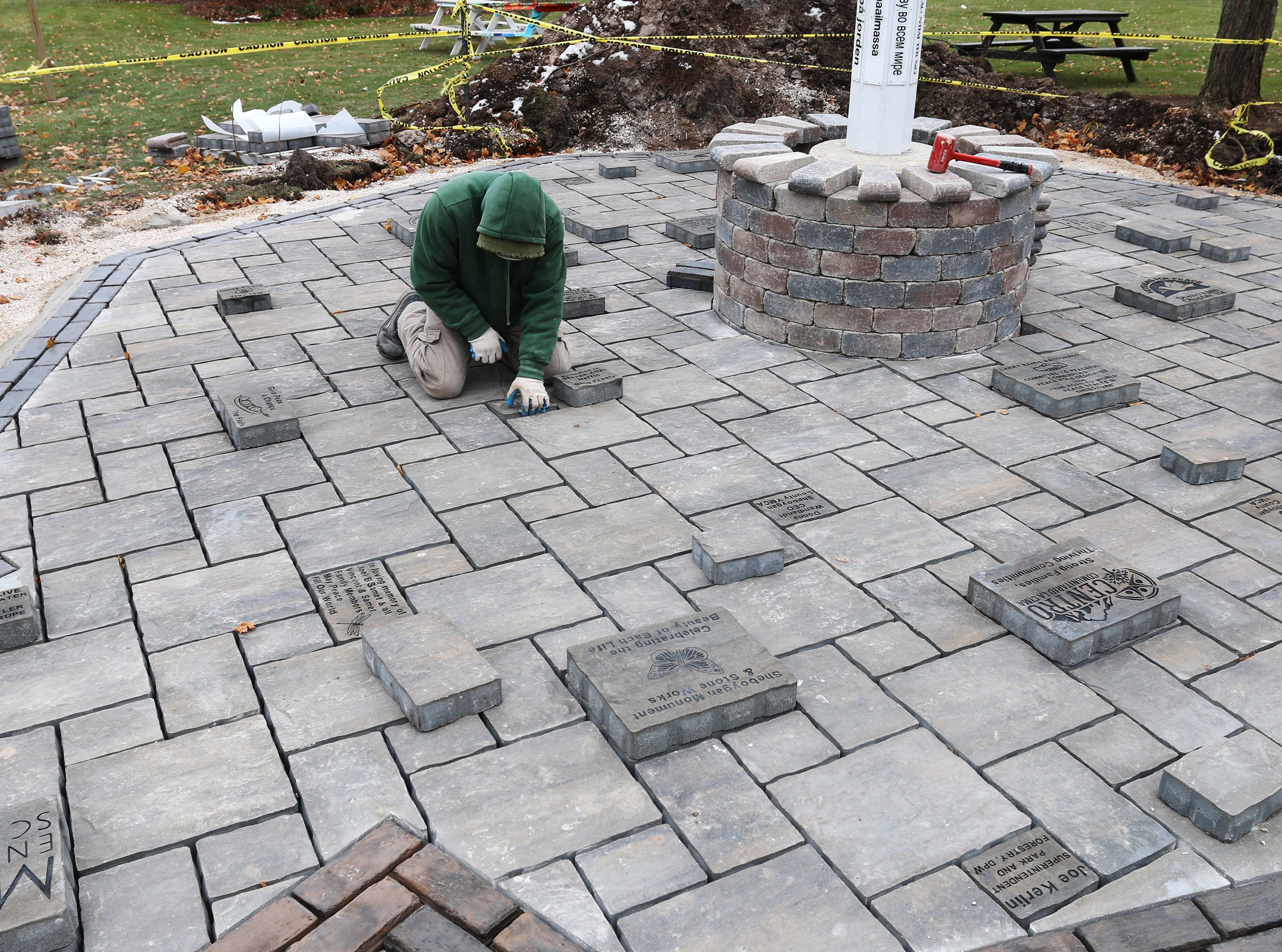 Bricklayer Mike Prahl, in green, installs engraved paver blocks for the first phase of renovations slated for Sheboygan Peace Park, Friday, November 16, 2018, in Sheboygan, Wis. For more information go to: https://sheboyganpeacepark.org/