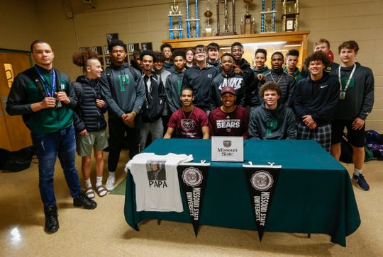 Members of the Parkview High School basketball team surround Tyem Freeman, seated at center, after he signed his letter of intent to play basketball at Missouri State University on Friday, Nov. 16, 2018.