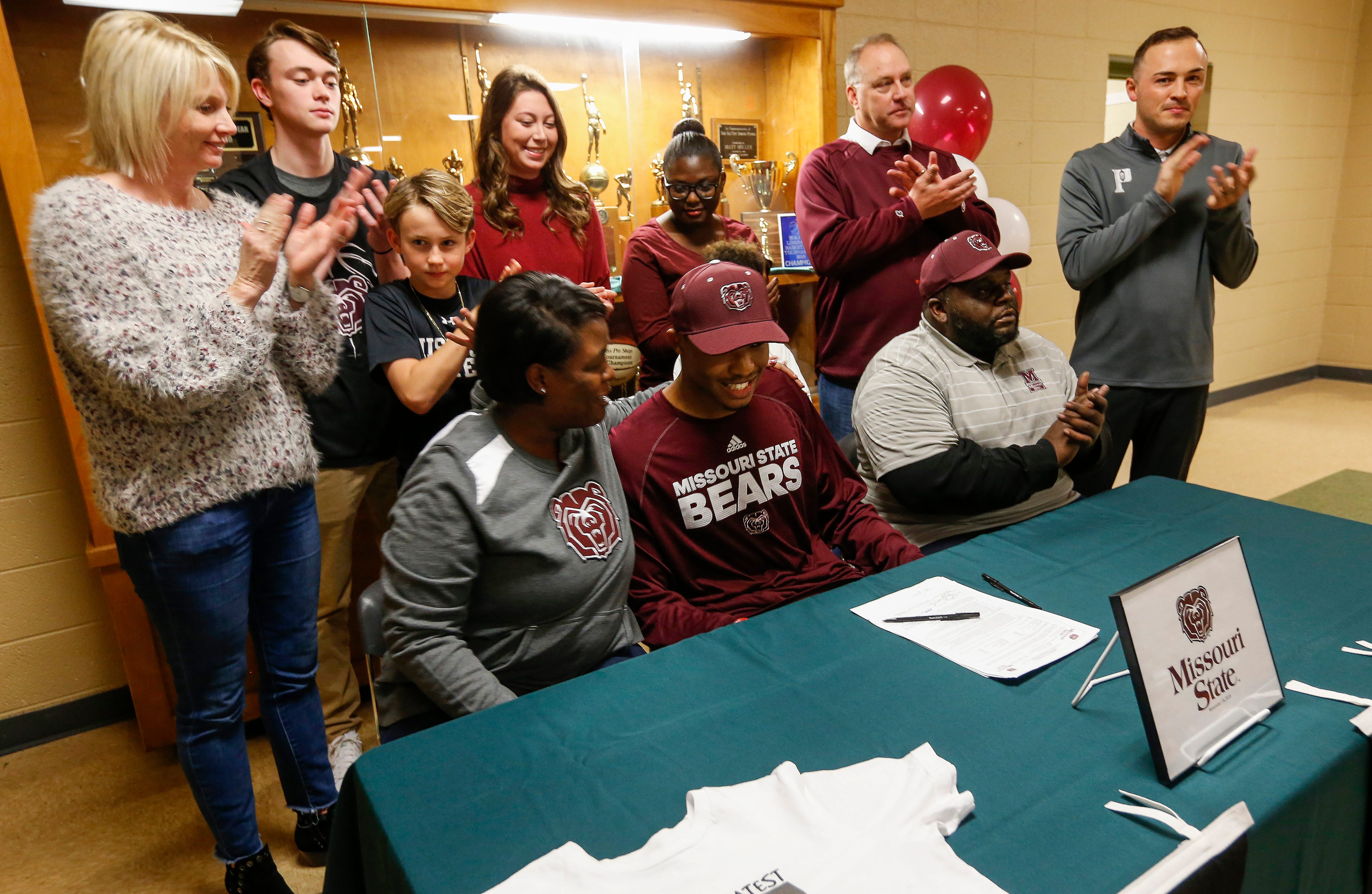 LaToya Branch puts her arm around Parkview High School forward Tyem Freeman after he signed his letter of intent to play basketball at Missouri State University on Friday, Nov. 16, 2018.