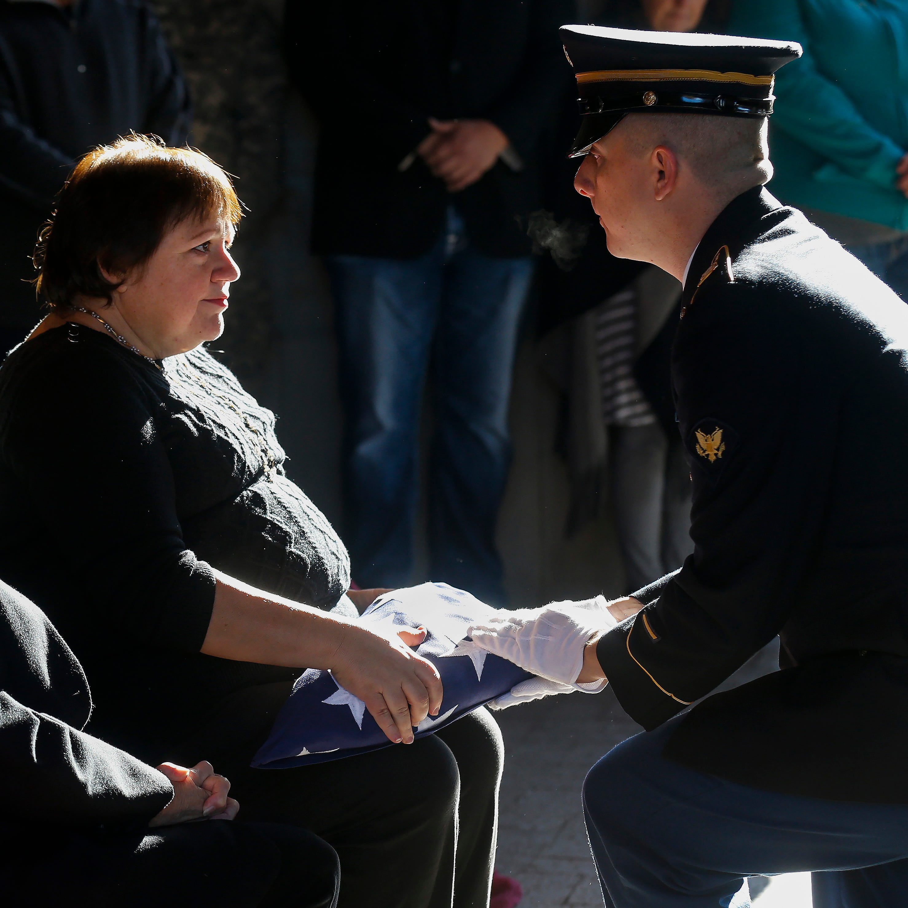 On behalf of a grateful nation, Spc.  Nathan Smith, a member of the Missouri National Guard, presents the U.S. flag to Annajean Shields during the funeral of Army veteran Michael Hiers at the Missouri Veterans Cemetery on Friday, Nov. 16, 2018.