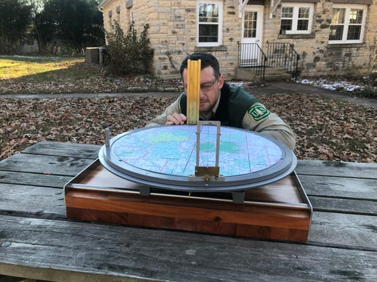 A Forest Service employee shows how a  lookout would use an alidade sighting device in the top of a fire tower to identify the location of a forest blaze.