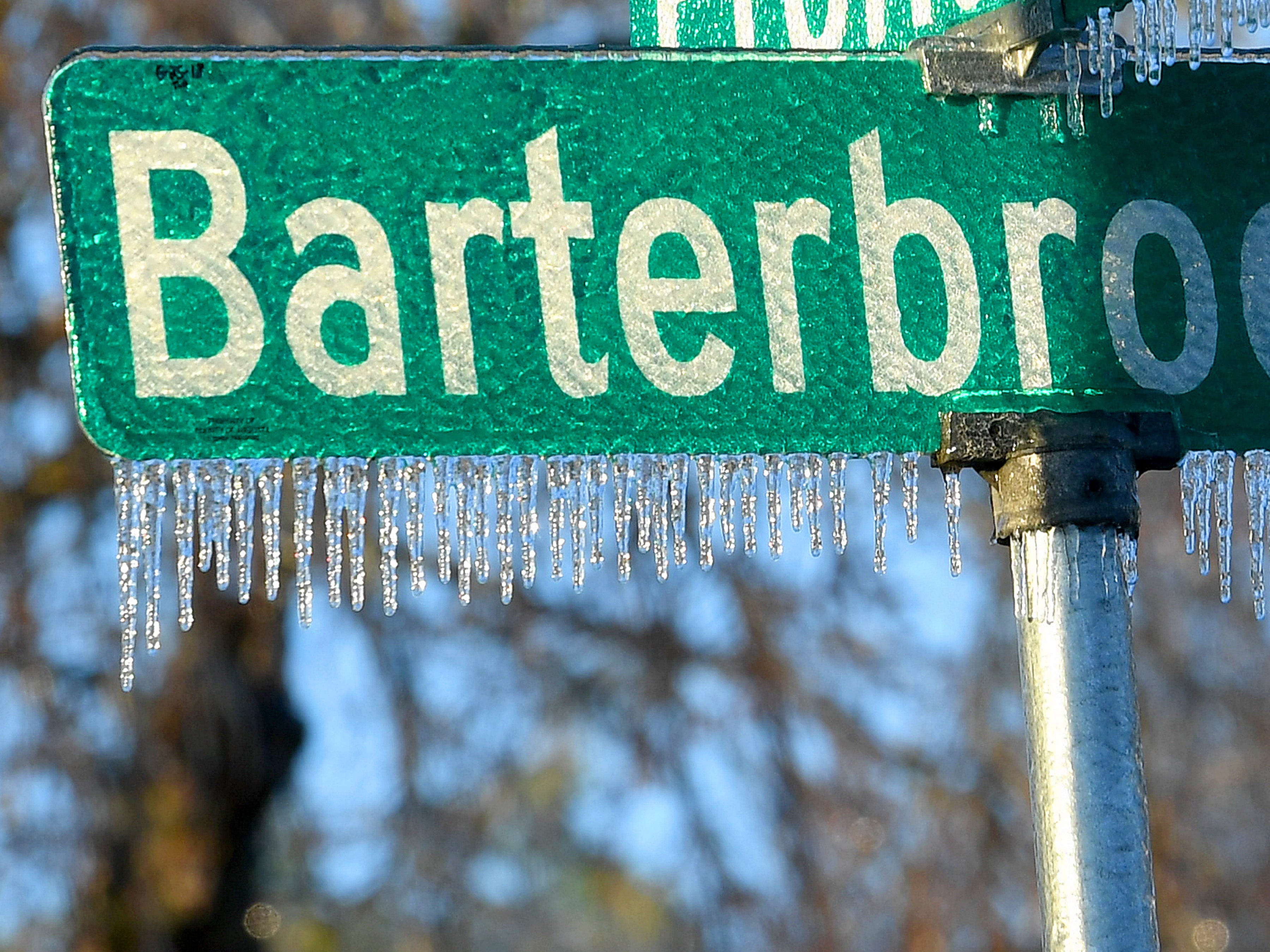 Ice covers and hangs from a Barterbrook Road street sign on an ice-covered Friday morning, Nov. 16, 2018.