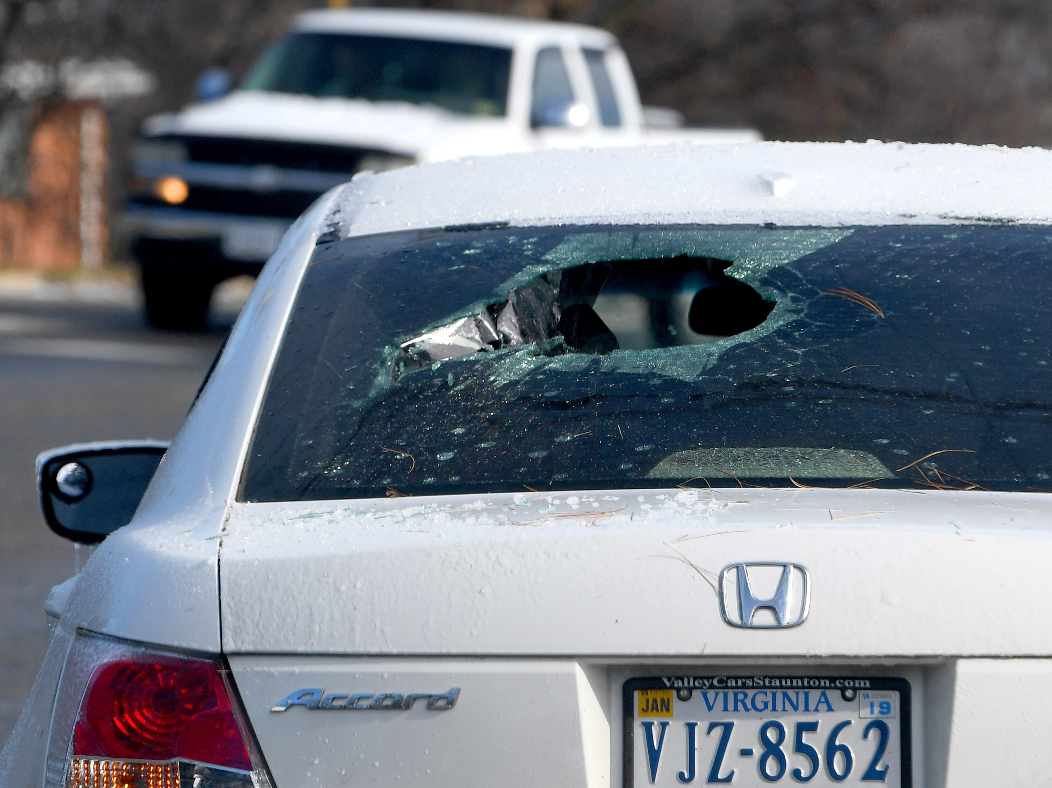 A car stopped at an intersection on Frontier Drive has a hole in the back window, possibly damage from a fallen limb, in the wake of an ice storm Friday, Nov. 16, 2018.